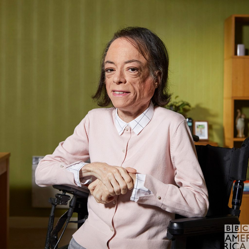 Liz Carr plays Meg wearing a pink cardigan, white checked shirt and grey trousers with arms folded in her wheelchair smiling knowingly.